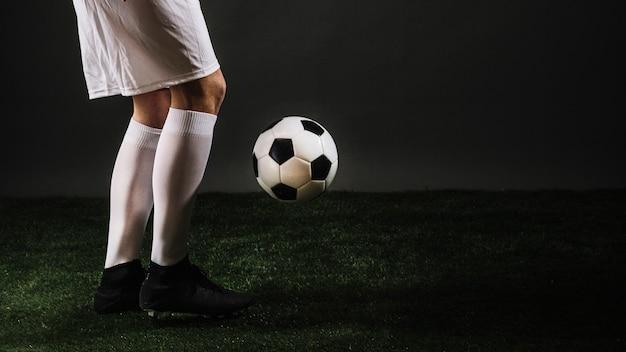Crop soccer player juggling ball in dark studio