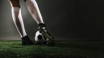 Crop soccer player kicking ball