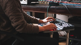 Crop sound engineer working at studio