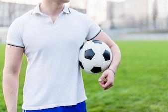 Crop sportsman carrying soccer ball