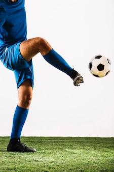 Crop sportsman kicking soccer ball