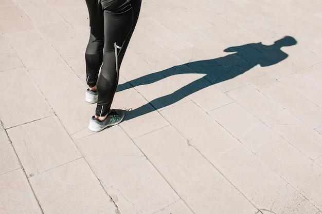 Ritaglia lo sportivo in piedi sul marciapiede