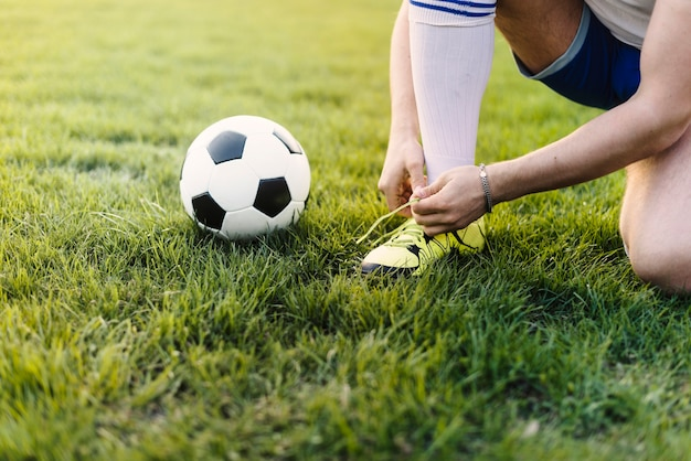 Crop sportsman tying laces on field