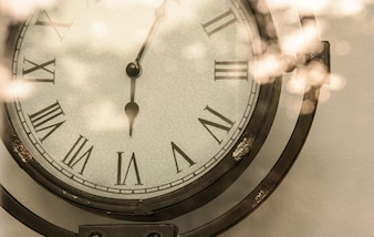 Crop steel Vintage analog clock and bright flare reflexing  in sepia