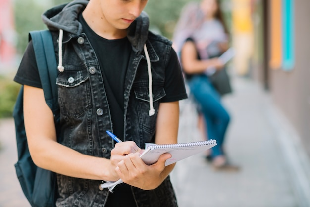 Crop student with notepad at street