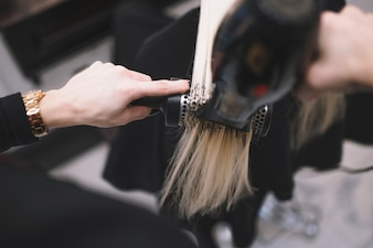Crop stylist setting hair with brush