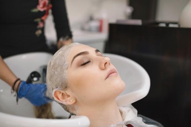 Crop stylist washing hair with shampoo