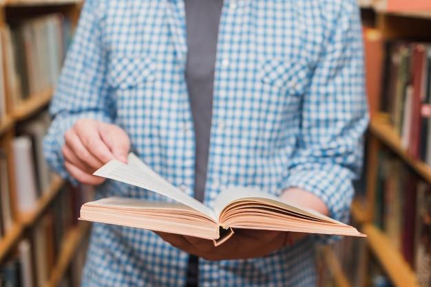 Ritaglia l'adolescente sfogliando le pagine del libro