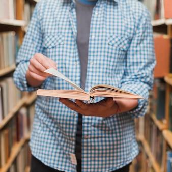 Crop teenager reading book between bookcases