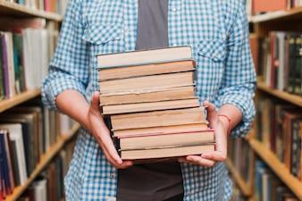 Crop teenager with books between bookshelves