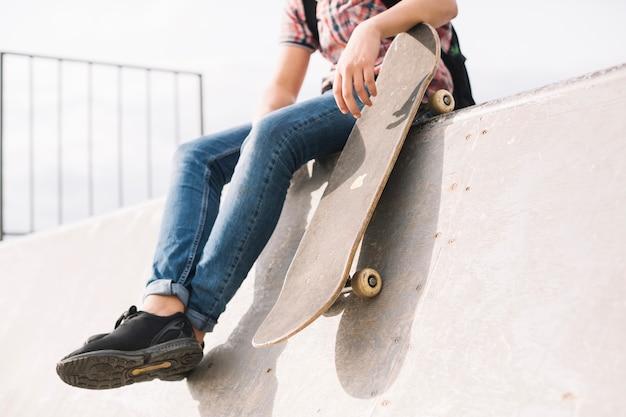 Crop teenager with skateboard sitting on ramp