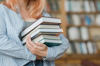 Crop teenager with stack of books