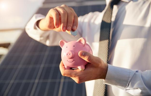 인식할 수 없는 사업가가 저렴한 대체 에너지의 개념으로 흐릿한 태양광 패널에 서서 돼지 저금통에 동전을 삽입합니다.