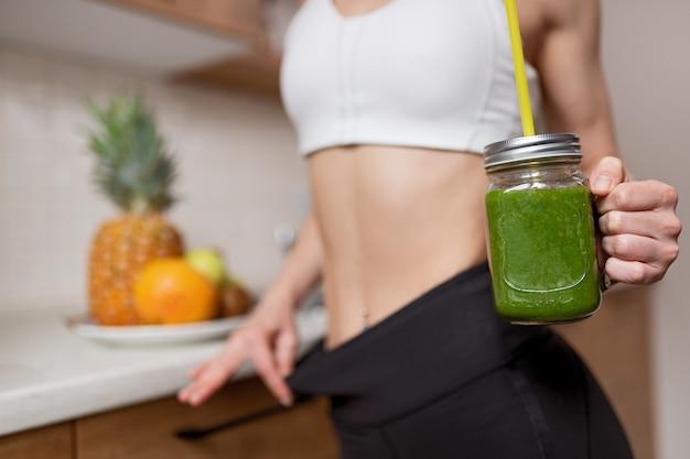 아침에 신선한 과일과 함께 부엌 카운터에 서있는 동안 건강한 녹색 해독 스무디와 유리 항아리를 들고 인식 할 수없는 슬림 여성 자르기