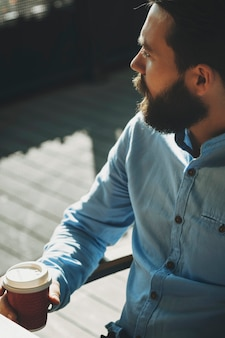 Crop view of bearded male in light shirt sitting outdoors with closed paper cup with tea or coffee and looking away with sunlit pavement on blurred background
