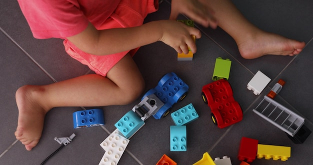 Crop view from above of little boy sitting on gray floor and playing with plastic colorful construction toy