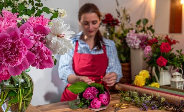Стеклянная ваза crop view с цветущими пионами продавец цветов флористический бизнес