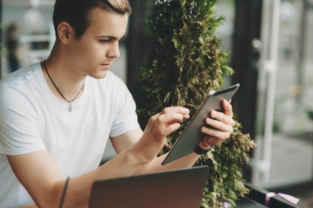 近くに緑の植物とラップトップとテーブルに座っているタブレットに取り組んでいる白いシャツの魅力的な男性の作物のビュー