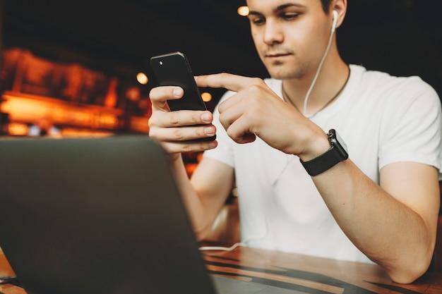 ノートパソコンと木製のテーブルに座って、ぼやけたオレンジ色のバーの背景に携帯電話を使用することに集中している白いシャツとイヤホンの魅力的な男性のトリミングビュー