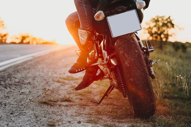 日没に対して世界中を旅しながら自転車に座っているバイカーの足のトリミングビュー。