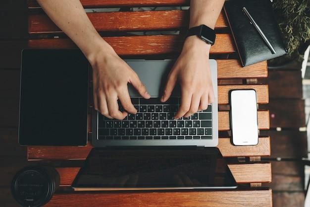 가제트와 노트북이 위에서 주위에 누워있는 나무 판자 테이블에 서있는 노트북을 사용하는 남성 손의 자르기보기