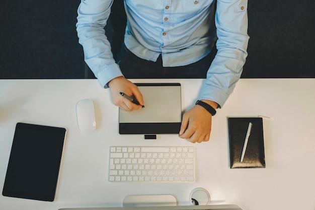 컴퓨터와 노트북 흰색 테이블에 앉아 위에서 그리기 태블릿을 사용하는 우아한 파란색 셔츠에 남성의 자르기보기
