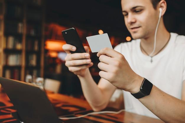 スマートフォンを保持し、名刺から番号をダイヤルし、笑顔でテーブルの上のラップトップでカフェのイヤホンに座っている若い男の作物のビュー