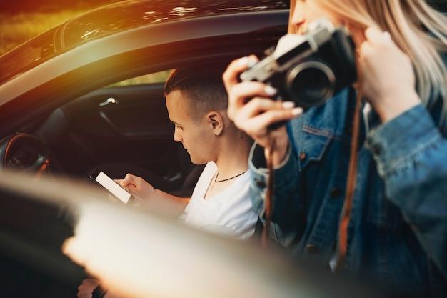 스마트 폰으로 운전석에 앉아 젊은 남자를보고 손에 카메라와 함께 열린 차 문에 서 캐주얼 의류에 자르기보기 여자