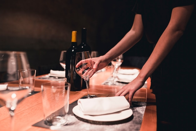 Crop waitress arranging glasses on table