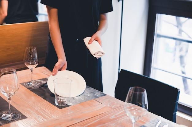 Ritaglia la cameriera mettendo il piatto sul tavolo