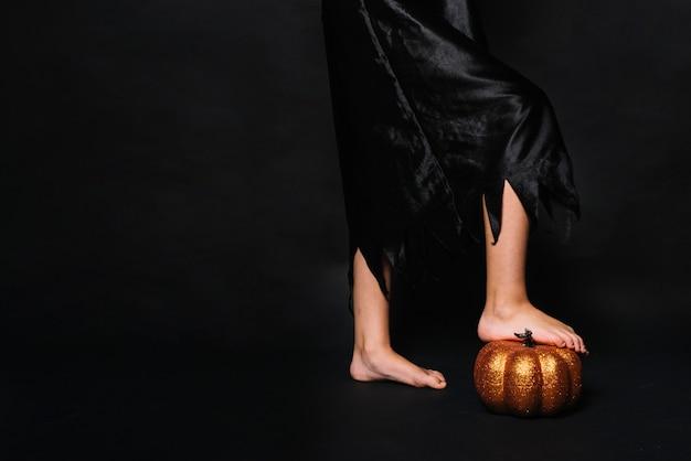 Crop witch stepping on pumpkin