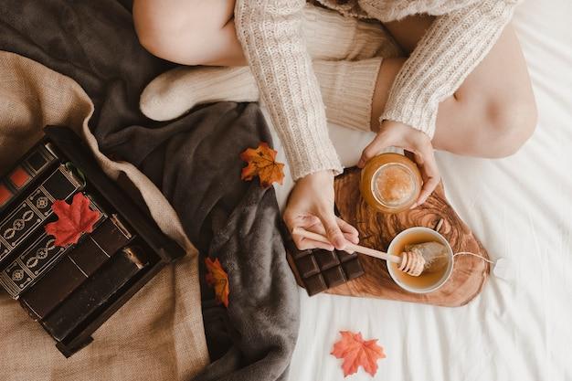Crop woman adding honey to tea