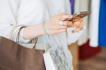 Crop woman browsing smartphone in shop