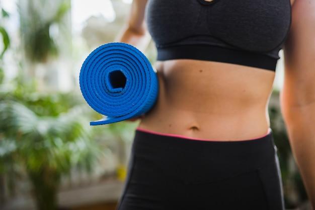 Crop woman carrying yoga mat