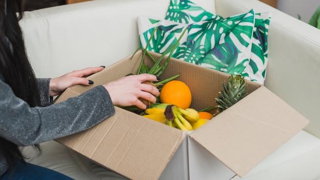 果物の小包をチェックする作物の女性
