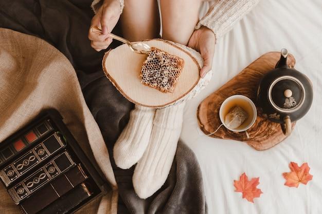 Crop woman eating honeycomb near books and tea