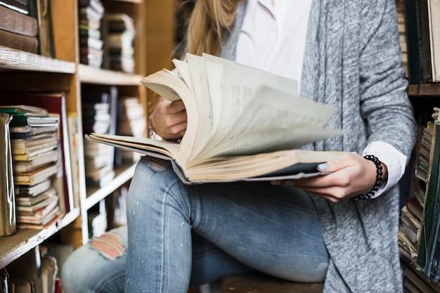 Ritaglia la donna sfogliando le pagine del libro
