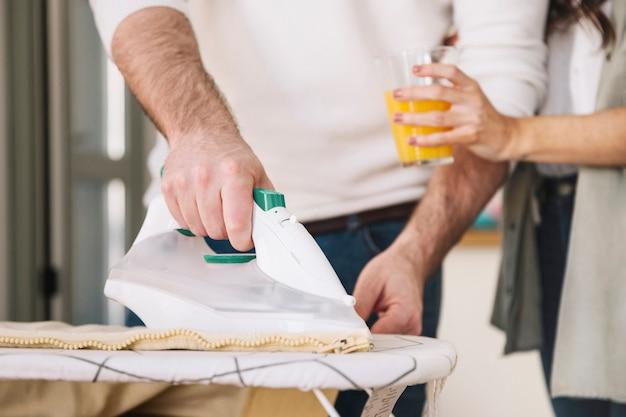 Crop woman giving juice to ironing man