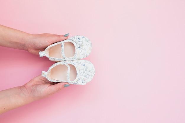 Donna della coltura che tiene le scarpe di bambino