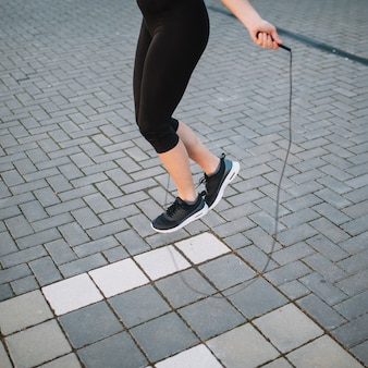 Crop woman jumping with rope on street