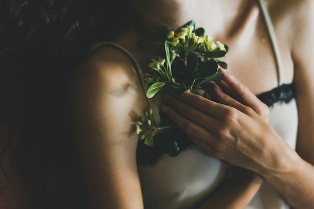 Crop woman keeping flowers near chest