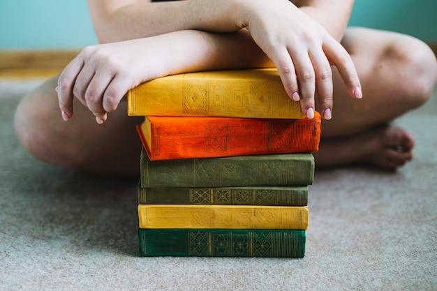 書籍の積み重ねの近くで作物の女性
