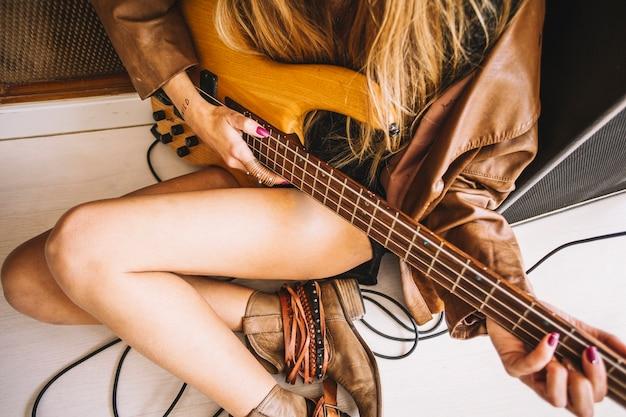Crop woman playing guitar near amplifier