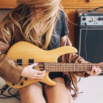 Crop woman playing guitar near cupboard