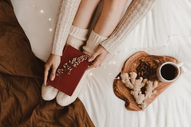Crop woman putting book on legs near tea and snacks