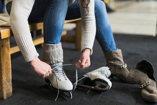 Crop woman putting on ice skates