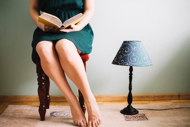 Crop woman reading near lamp
