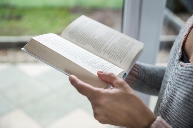 窓の近くで女性の読書を刈る