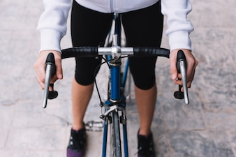 Crop woman riding bike