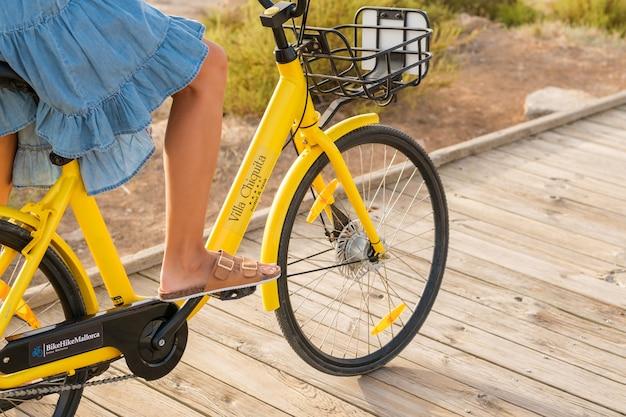 遊歩道に沿って黄色い自転車に乗る作物の女性